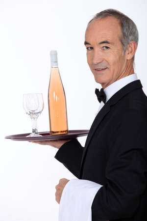 Waiter carrying bottle of wine on tray Stock Photo - 15673140