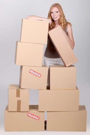 pakiety: Młoda kobieta otoczona kartony
