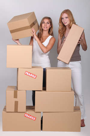 Young women stacking boxes photo