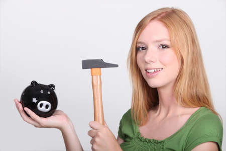provisions: Young female holding piggy bank and hammer