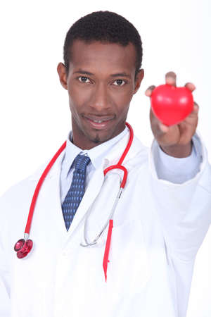 Hospital doctor with a plastic heart in the palm of his hand photo