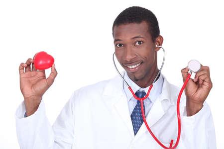 plastic heart: Medico in possesso di uno stetoscopio e un cuore di plastica Archivio Fotografico