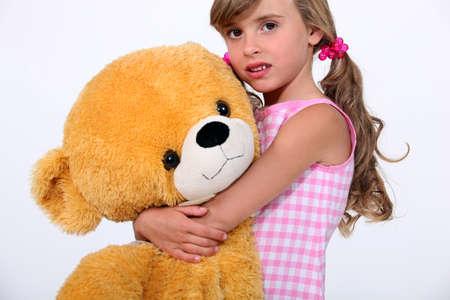8 9 years: Little girl holding giant teddy bear Stock Photo