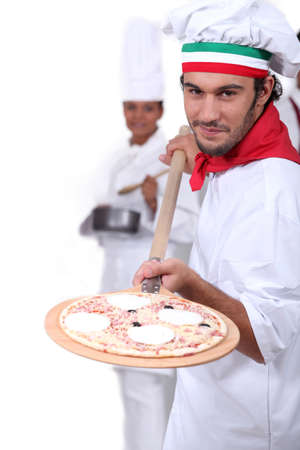 displaying: Pizza maker displaying his pizza