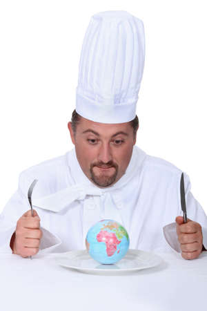 circumstances: cook with globe on a plate Stock Photo