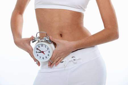 fit woman holding a clock photo
