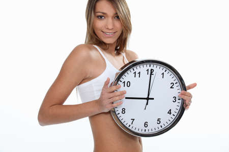 young sporty woman showing a clock photo