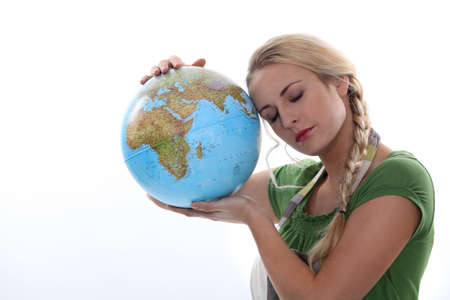 Woman in green resting her head against a large globe photo