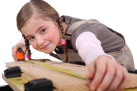 porgere: una ragazza bambino misura una tavola Archivio Fotografico