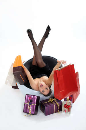 elicit: Excited woman sat with shopping bags