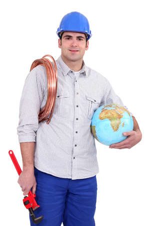 Tradesman holding a globe, a coiled copper wire and a pipe wrench photo