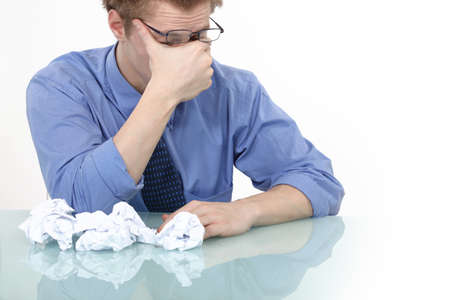 worried executive: tired businessman rubbing his eyes