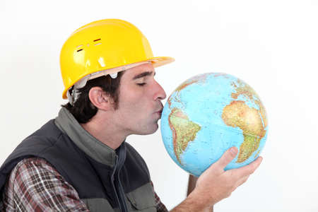 africa kiss: A construction worker kissing a globe  Stock Photo