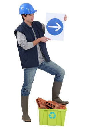hard way: Labourer holding a traffic sign Stock Photo