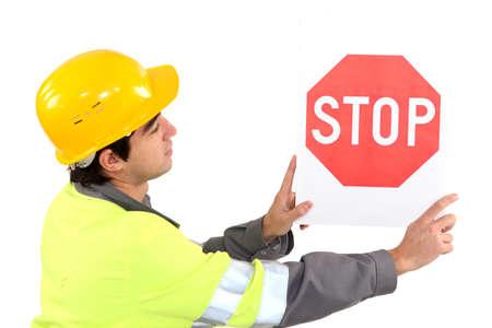 roadwork: Laborer showing stop sign