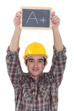 scholar: A construction worker holding a slate