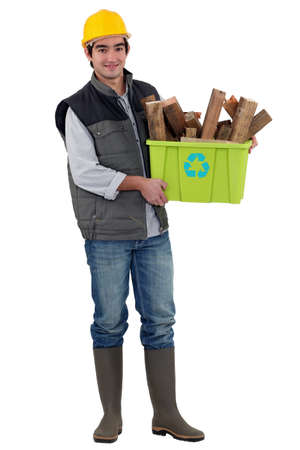 garbage disposal: Man holding box of wood to be recycled