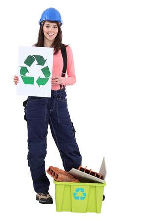 logo recyclage: jeune maçon femme tout sourire tenant logo de recyclage