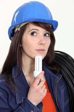 Thoughtful woman holding a compact fluorescent lamp photo