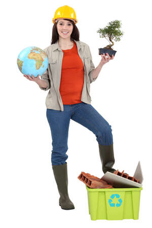 cute brunette apprentice holding globe with foot resting on recycling tub photo