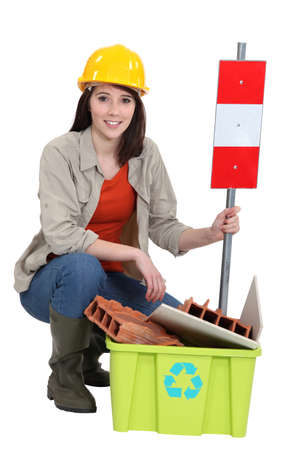 Female builder kneeling by recycle box photo