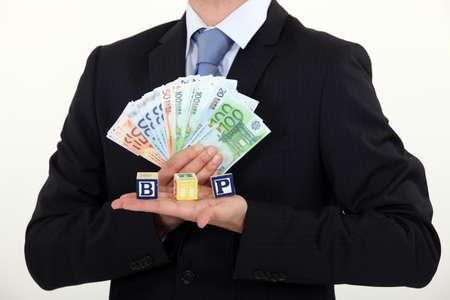 btp: Businessman holding bills and toy blocks Stock Photo