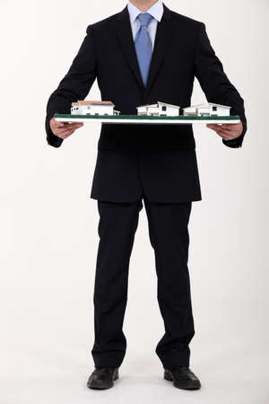 Businessman holding a model of a housing estate photo