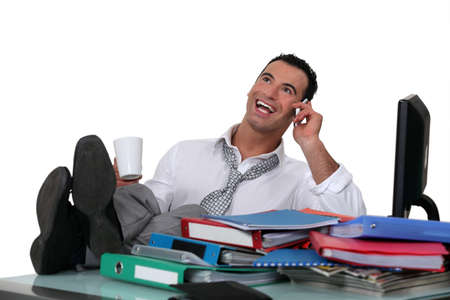 pies masculinos: Empleado de oficina informal con los pies sobre el escritorio Foto de archivo