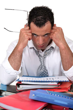 Frustrated businessman with files photo