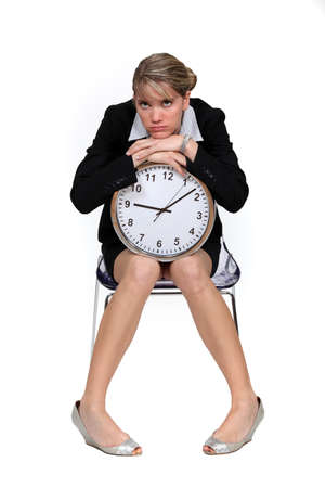 time deficit: Upset woman sat with clock