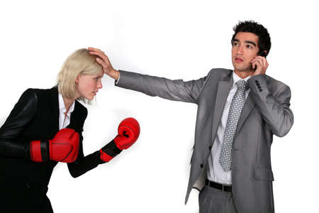 counterparts: businesswoman with boxing gloves and male colleague on the phone