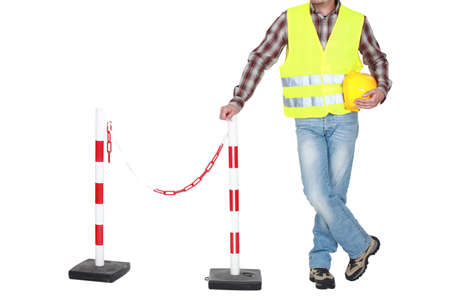 high visibility: Traffic guard standing beside a barrier