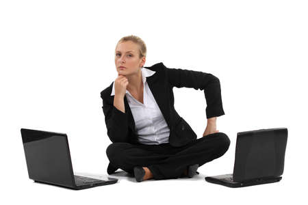Pensive businesswoman sat with two laptops photo