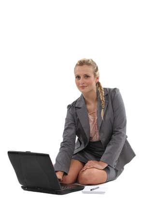 assis par terre: Femme d'affaires travaillant sur le plancher
