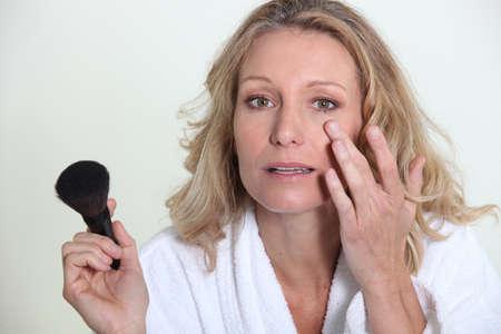 mujer maquillandose: La mujer rubia aplicar el maquillaje