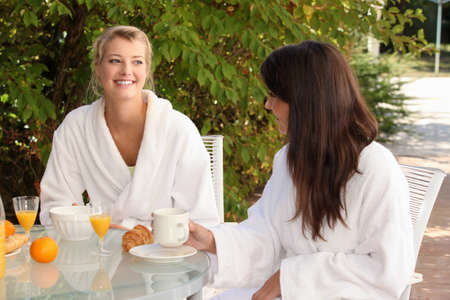 toweling: Two young women breakfasting on the patio