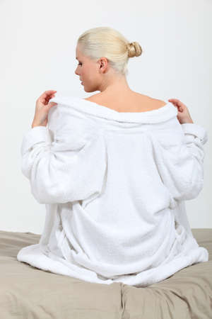 robes: A female model taking her bathrobe off on her bed