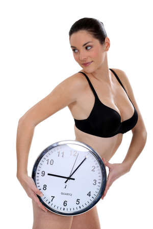 pregnant underwear: Woman in her underwear holding a large clock Stock Photo