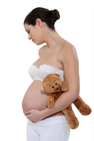 expectant mother: pregnant woman holding a teddy bear