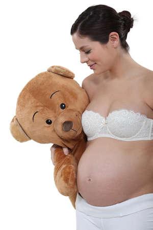 Pregnant woman holding a big teddy bear