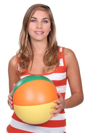 beach ball girl: Young woman holding an inflatable ballon  Stock Photo