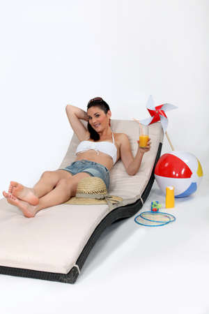 lounging: Attractive woman lying on a lounge chair on the beach