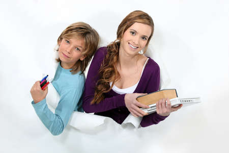 younger: female student holding books and younger brother Stock Photo