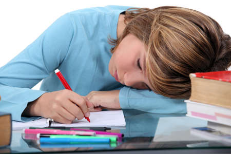 inadequate: Tired child doing homework Stock Photo