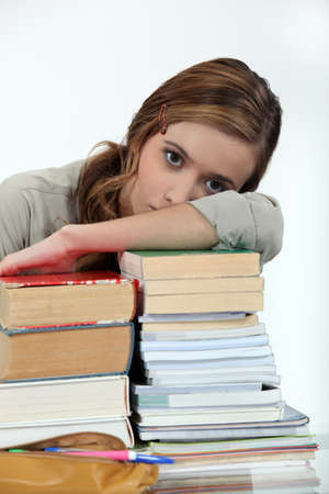 highlighted hair: Young woman laying her head on a stack of books Stock Photo