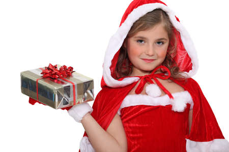 Little girl in a Santa costume with a wrapped gift photo
