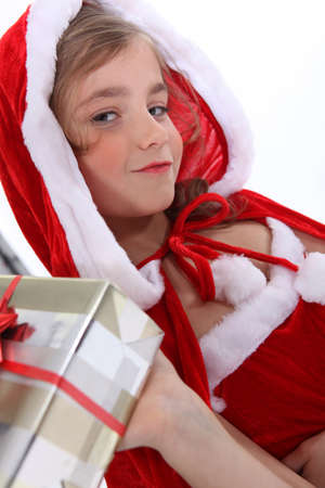 6 7 years: Little girl in a Santa outfit with Christmas presents
