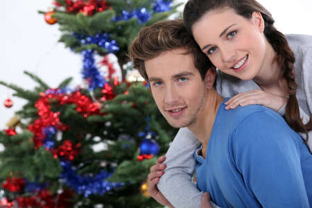 Couple gathered by Christmas tree photo