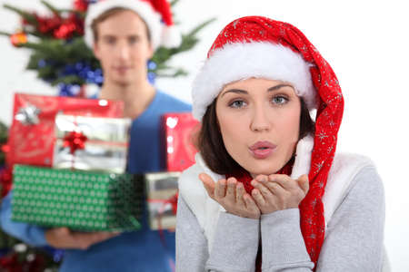 Woman with Christmas hat blowing kiss photo