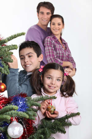happy parents with children decorating Christmas tree photo